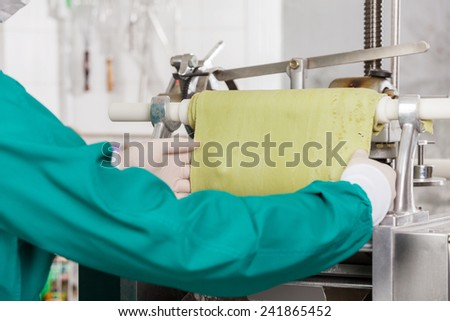 Cropped image of male chef processing green pasta sheet in machine at commercial kitchen