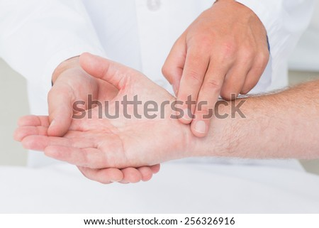Cropped image of male doctor checking patients pulse rate in clinic - stock photo