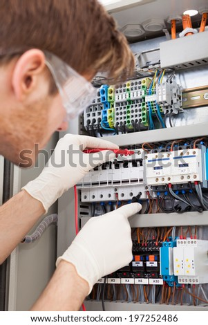 Cropped image of male electrical engineer examining fusebox with multimeter probe - stock photo