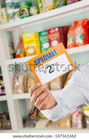 Cropped image of male owner holding discount sign in supermarket - stock photo