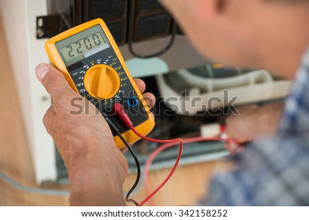 Cropped image of male repairman checking fridge with digital multimeter at home - stock photo