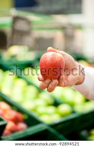 Cropped image of male's hand holding an apple at supermarket - stock photo