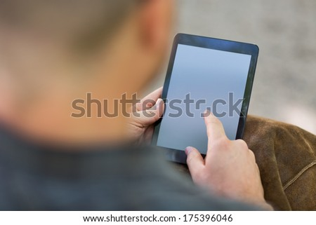 Cropped image of male university student using digital tablet at campus - stock photo