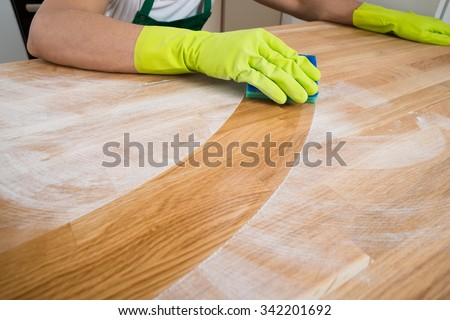 Cropped image of man cleaning dust on wooden table at home - stock photo