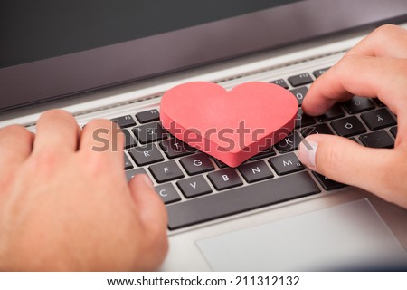 Cropped image of man dating online with heart shape on laptop - stock photo