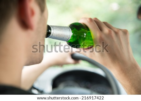 Cropped image of man drinking alcohol while driving car - stock photo