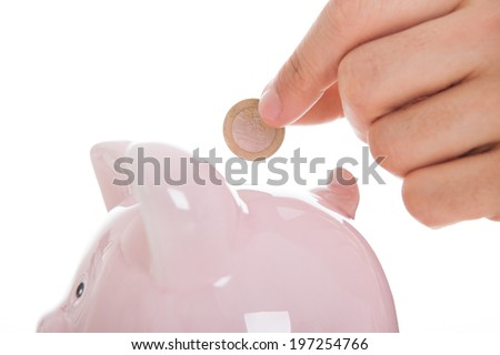 Cropped image of man inserting coin in piggybank against white background - stock photo