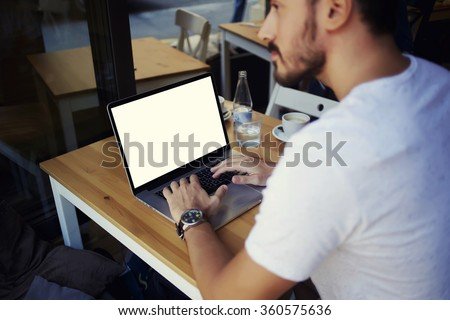 Cropped image of man learning on-line via laptop computer during lunch in cafe, male freelancer sitting in front open net-book with blank copy space screen for your text message or information content - stock photo
