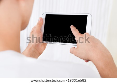 Cropped image of man using digital tablet at home - stock photo