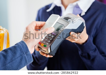 Cropped image of man using NFC technology to pay bill at cinema - stock photo