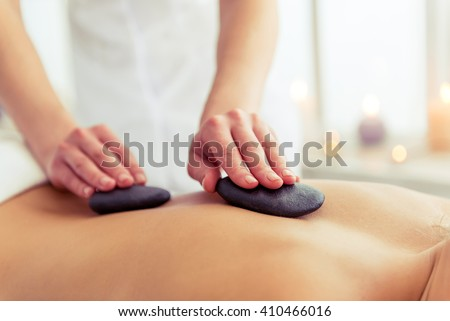 Cropped image of massage therapist putting spa stones on the back of beautiful blonde girl lying on a massage table - stock photo