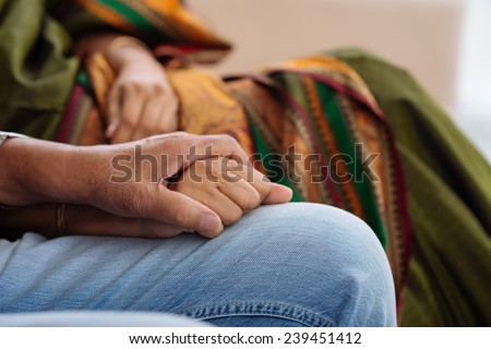 Cropped image of mature man holding a hand of his wife - stock photo
