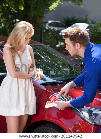 Cropped image of mechanic showing color samples to customer against car - stock photo