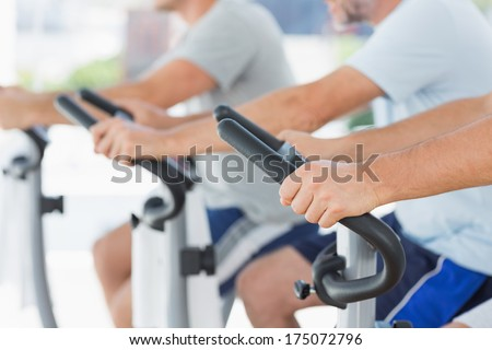 Cropped image of men using exercise bikes at fitness studio - stock photo
