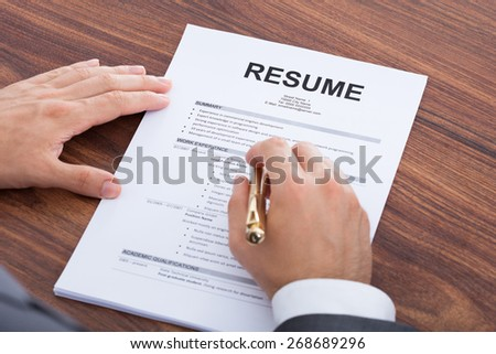 Cropped image of mid adult businessman analyzing resume at desk - stock photo
