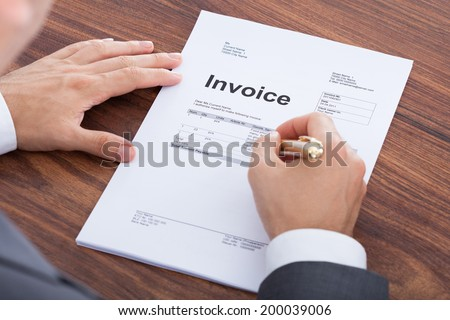 Cropped image of mid adult businessman calculating invoice at office desk - stock photo