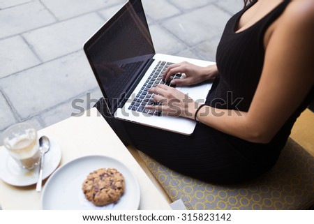 Cropped image of modern businesswoman work in internet via net-book while resting in cafe outdoors, young female keyboarding on laptop computer with blank empty screen for your information or content  - stock photo