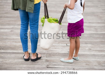 Cropped image of mother and daughter holding textile bag with groceries - stock photo