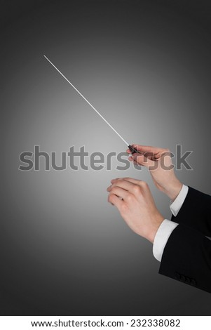 Cropped image of music conductor's hands holding baton over gray background - stock photo