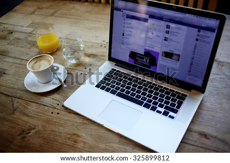 Cropped image of open net-book with screen for information content or advertising text message, there is portable laptop computer, cup of coffee and glass of juice on wooden table in cafe interior - stock photo