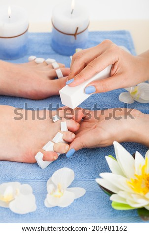 Cropped image of pedicurist filing toenails of woman in beauty salon - stock photo
