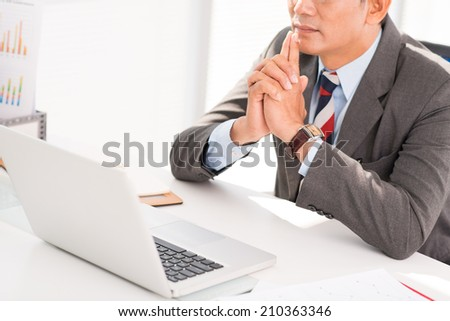 Cropped image of pensive businessman sitting on front of the laptop - stock photo