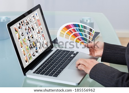 Cropped image of photo editor with color swatches working on laptop at desk