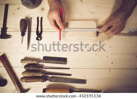 Cropped image of senior carpenter measuring wood in workshop - stock photo