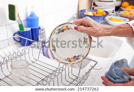 Cropped image of senior woman arranging plate in rack at kitchen counter - stock photo