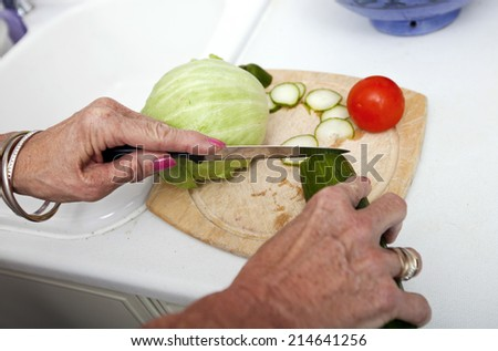 Cropped image of senior woman chopping vegetables on cutting board in kitchen - stock photo