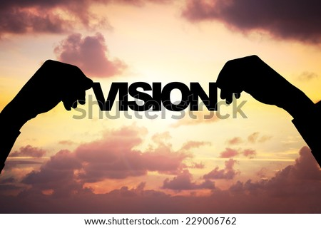 Cropped image of silhouette businessman's hands holding VISION word against cloudy sky during sunset - stock photo