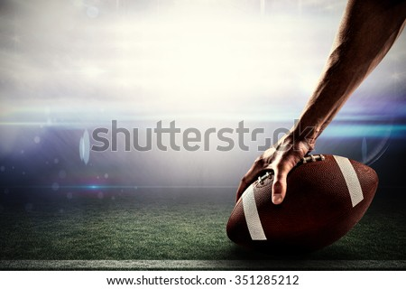 Cropped image of sports player holding ball against american football arena - stock photo