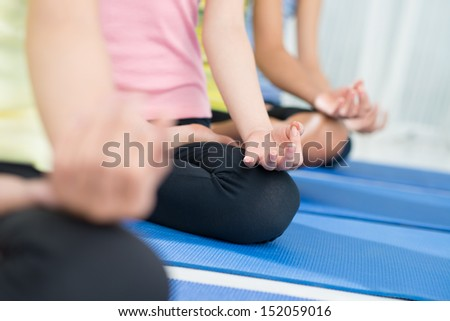Cropped image of sporty people meditating on the foreground