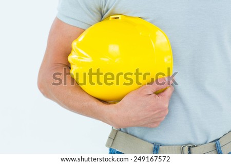 Cropped image of technician holding hard hat over white background