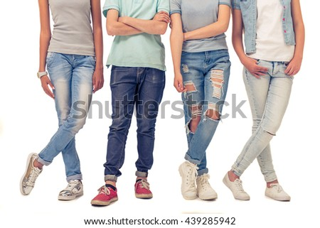 Cropped image of teenage boy and girls in jeans standing in row, isolated on white - stock photo
