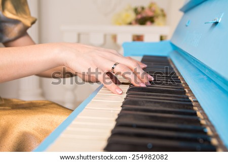 cropped image of the girl's hands on the piano keys. Close up of the hands of a young woman playing piano - stock photo