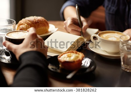 Cropped image of two people's hands at a table with coffees and pastry snacks, one person picking up their espresso while the other is writing in a notebook, possibly taking down an interview - stock photo