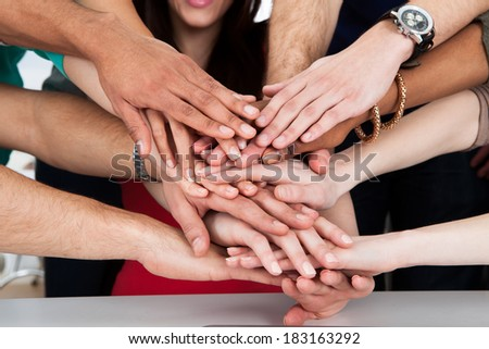 Cropped image of university students piling hands at desk - stock photo
