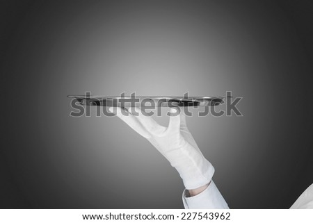 Cropped image of waiter's hand holding tray over gray background - stock photo