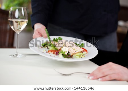 Cropped image of waitress serving fish dish at restaurant table - stock photo