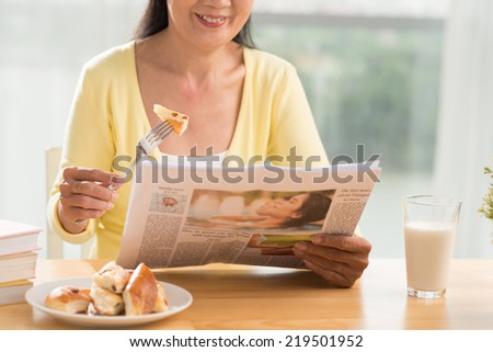 Cropped image of woman having breakfast and reading newspaper at home - stock photo