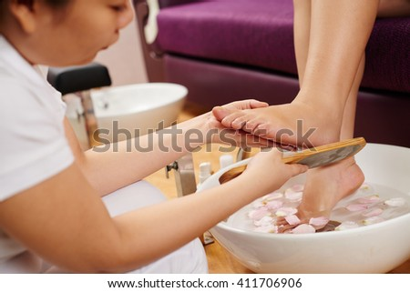Cropped image of woman having spa treatment for her feet in beauty salon - stock photo
