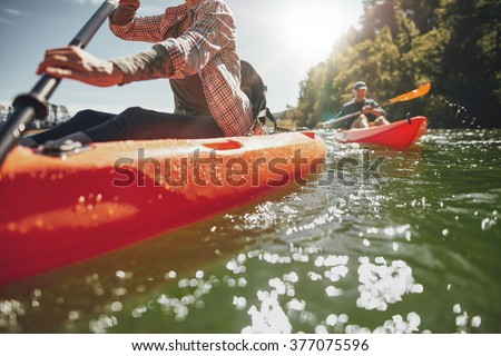 Cropped image of woman kayaking with a man in background. Couple canoeing in a lake on a summer day.