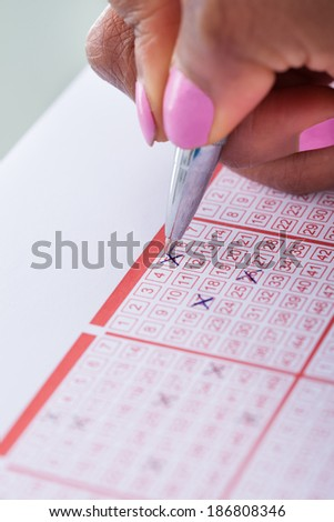 Cropped image of woman's hand marking numbers on lottery ticket with pen at table - stock photo
