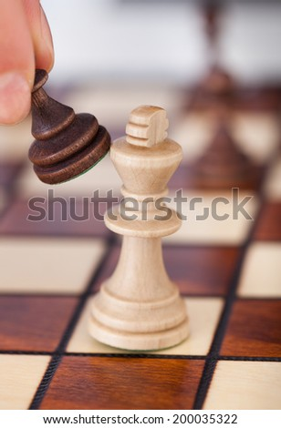 Cropped image of woman's hand playing chess on table - stock photo
