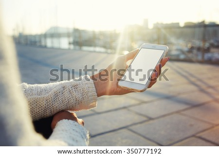 Cropped image of woman's hands holding cell telephone with blank copy space screen for your text message or promotional content, hipster girl using mobile phone while resting outdoors during free time - stock photo