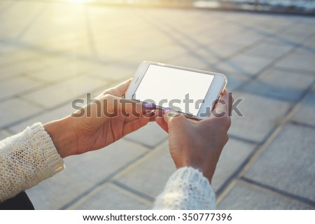 Cropped image of woman's hands holding cell telephone with blank copy space screen for your text message or advertising content, female watching video on smart phone while relaxing in the fresh air  - stock photo