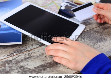 Cropped image of woman using credit card and touchpad for online tour booking on wooden table  - stock photo
