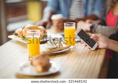 Cropped image of woman using phone while having breakfast with colleagues in office - stock photo