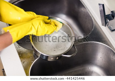 Cropped image of woman wearing gloves washing utensils at home